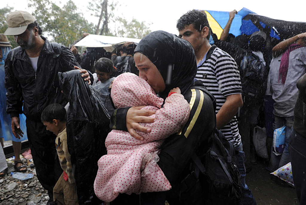 A migrant holds a child under the rain close to the border crossing between Greece and Macedonia, near the village of Idomeni